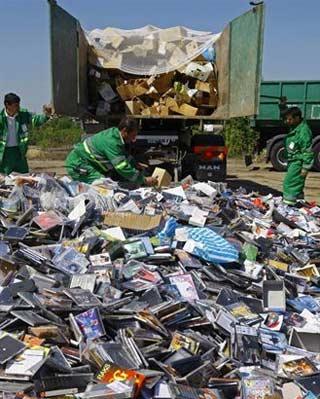Operarios deshechan copias de CDs. REUTERS