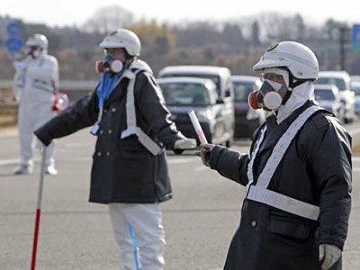 Agentes de la policía nipona evacúan a la gente en las proximidades de la central nuclear en Fukushima.-