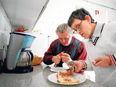 Fernando (izda.) y Miguel preparan un sándwich; abajo, Pepi elabora pulseras en la Fundación Gil Gayarre. - MÓNICA PATXOT