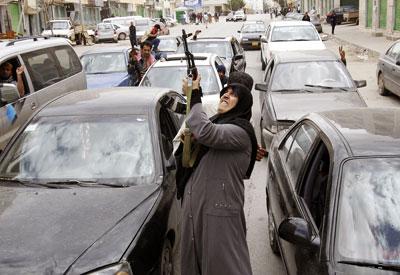 Una mujer dispara un AK-47 para celebrar la noticia de que había comenzado la operación internacional contra las tropas de Gadafi en Bengasi. - REUTERS