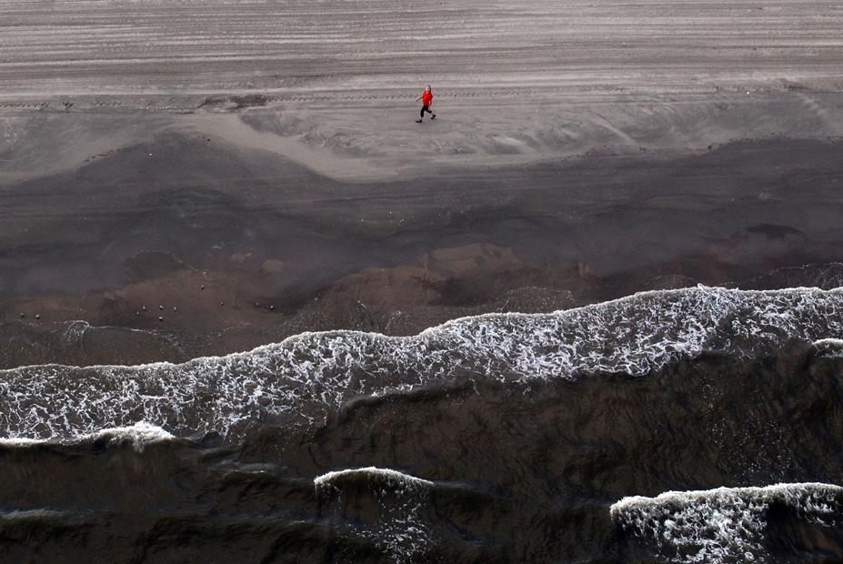 Mujer camina por la costa de Luisiana, afectada por el vertido de petróleo
