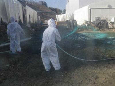 Operarios echan resina a un reactor dañado. REUTERS