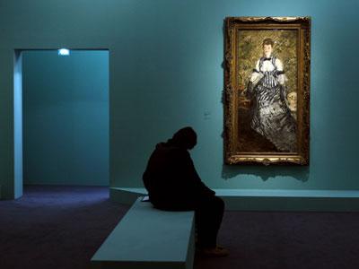 Una visitante de la exposición, junto al cuadro Dama en traje de noche'. afp