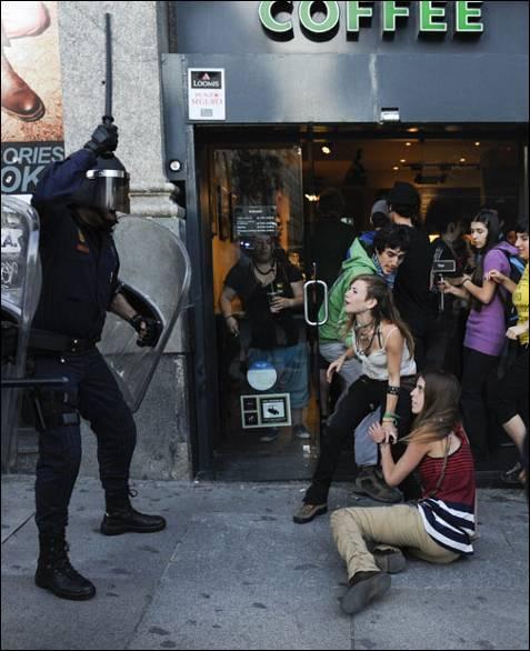 Un antidisturbios amenaza a dos manifestantes durante la marcha.