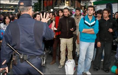 Agentes de Policía frente a un grupo de jóvenes presentes en el acampada de la Puerta del Sol de Madrid.
