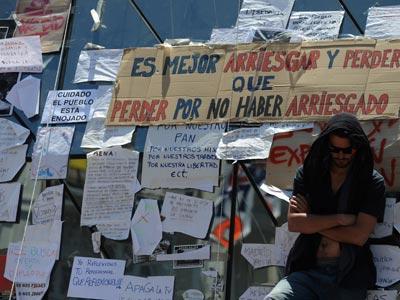 Uno de los participantes en la movilización junto a varios carteles situado en la Puerta del Sol de Madrid. fernando sánchez