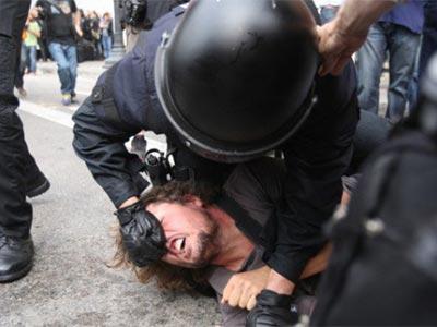 Un Mosso d'Esquadra agrediendo a uno de los acampados de la Plaza de Catalunya, Barcelona, el pasado viernes.