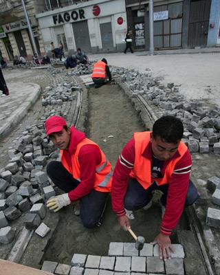 Trabajadores en una calle de Bucarest (Rumania).-