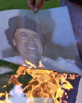 Un rebelde quema una fotografía de Gadafi.