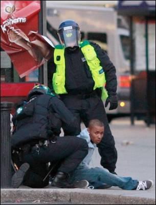Dos agentes detienen a un joven ayer en Enfield. Reuters