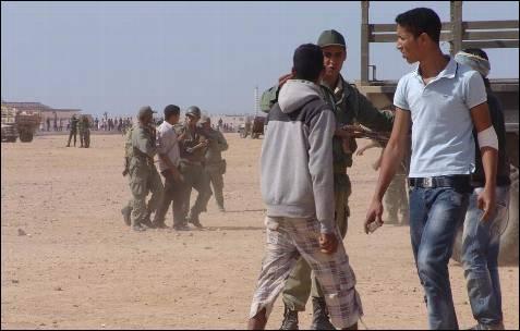 Los soldados de Rabat charlan con marroquíes que portan piedras en sus manos.