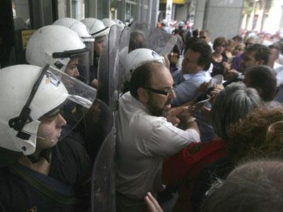 Empleados del Ministerio de Finanzas pelean con policías antidisturbios en la sede del ministerio en Atenas.