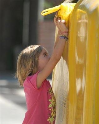 Una niña deposita una bolsa de residuos en un contenedor amarillo.