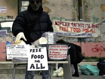 Un voluntario de una ONG reparte comida caliente a gente necesitada - EFE /ALKIS KONSTANTINIDIS
