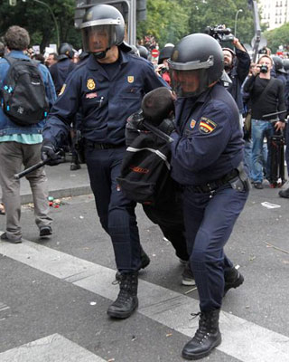 Dos policías conducen a uno de los detenidos hoy en la protesta del 25S.
