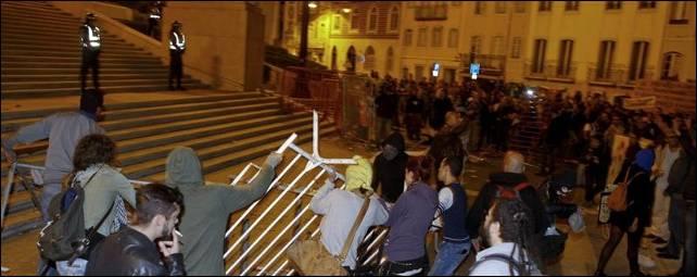 Manifestantes tratan de tumbar una barrera durante una manifestación por el presupuesto presentado por el Gobierno ante el Parlamento - EFE