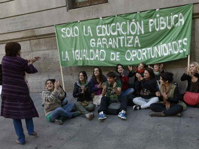Una mujer aplaude a un grupo de estudiantes que protestan frente a un colegio de Madrid. REUTERS/Andrea Comas