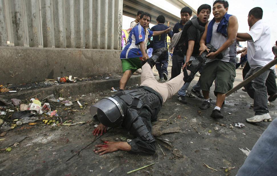 Un policía antidisturbios es arrastrado por los manifestantes, después de haber sido derribado de su caballo, durante las protestas de los comerciantes del mercado de La Parada, en Lima, tras la decisión de las autoridades locales de designar otro punto de distribución como único mayorista de la capital peruana.
