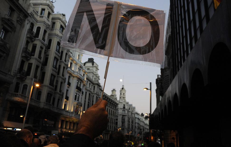 Un manifestante, sostiene una pancarta con la palabra 'No'.