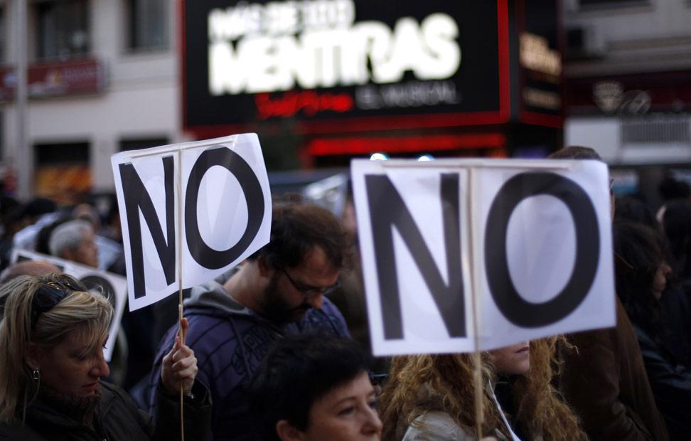 Dos pancartas con la inscripción 'No', con un cartel de fondo del musical 'Más de 100 mentiras', que se anuncia en la madrileña Gran Vía.