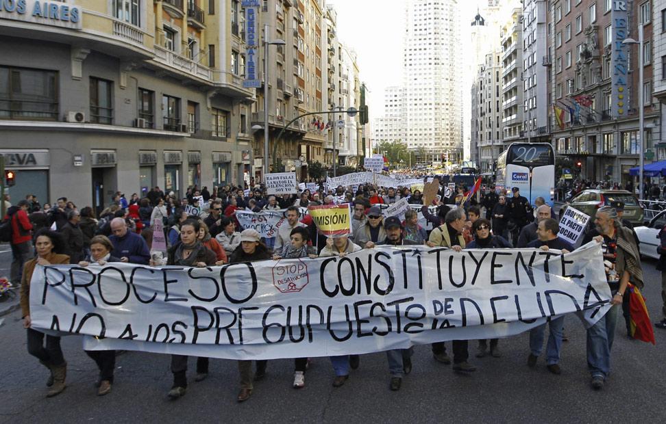 Varias personas portan una pancarta a su paso por la madrileña calle de Gran Vía durante la manifestación 'no comunicada' convocada esta vez contra los presupuestos generales del Estado.
