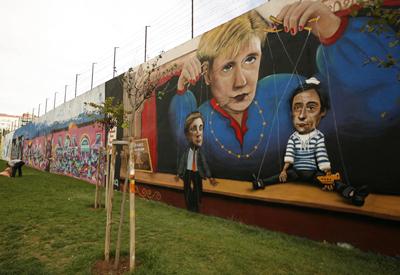 Una pintada en Lisboa sobre Merkel, sujetando los hilos que manejan al primer ministro protugués, Pedro Passos Coelho.
