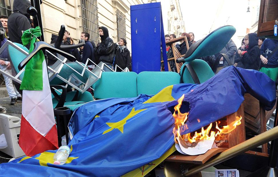 Unos manifestantes queman una bandera europea en la manifestación en Turín.
