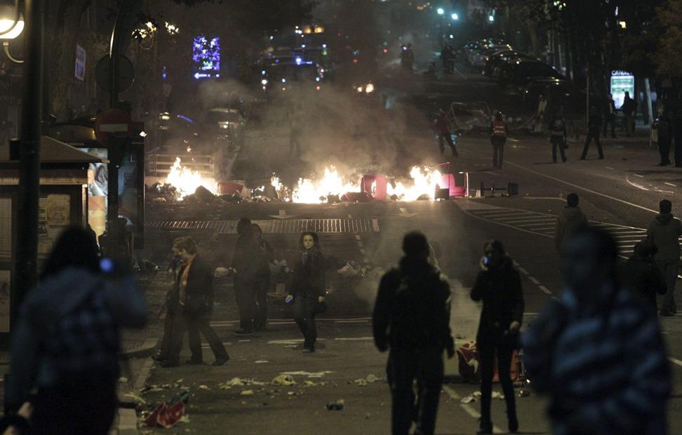 Vista del madrileño Paseo del Prado con las llamas producidas por la quema, entre otros, del mobiliario urbano, durante la concentración - EFE