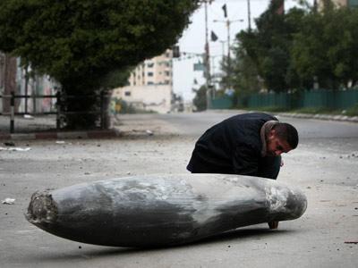 Un policía de Hamás inspecciona uno de los cohetes caídos desde Israel en la franja de Gaza. AFP