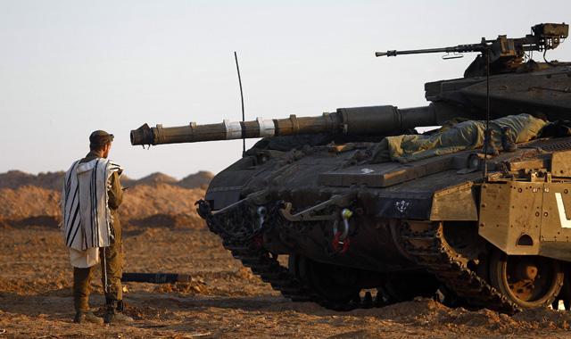 Un soldado israelí reza delante de su tanque.