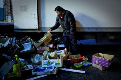 Un hombre busca restos de comida en la basura. AFP