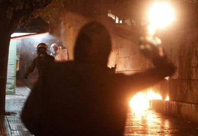 Un manifestante se enfrenta a un antidisturbios en la Plaza Syntagma, de Atenas.