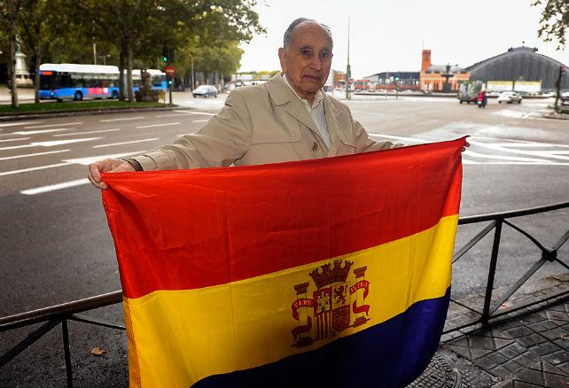 David Solomon posa junto a la bandera republicana frente a la Estación de Atocha (Madrid)