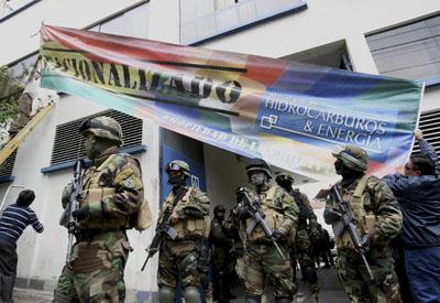 Soldados bolivianos a la entrada de la planta de Electropaz, filial de Iberdrola, donde dos operarios cuelgan el cartel de 'nacionalizada'.