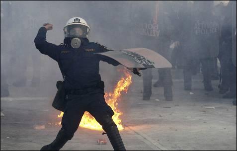 Un policía antidisturbios lanza una piedra contra las manifestantes delante del Parlamento.