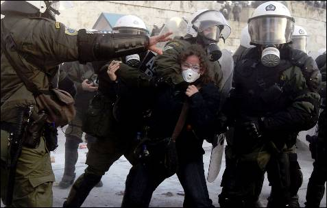 Las fuerzas griegas se llevan agarrada por el cuello a una manifestante.