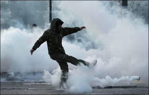 Un manifestante chuta un bote de gas lanzado por la policía.