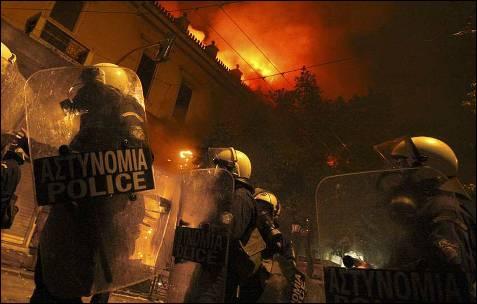 Los antidisturbios avanzan entre edificios en llamas.