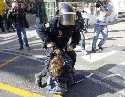 Un agente de policía forcejea con un joven. -