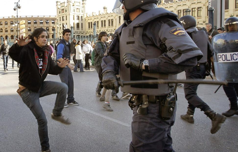 Antidisturbios intentando golpear a una joven con la porra