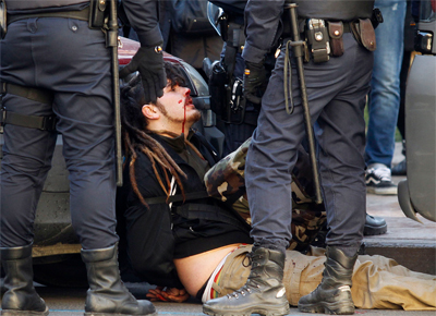 Un joven herido es retenido por varios agentes. -