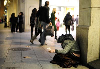 Una mujer pide limosna en una calle de Barcelona.-