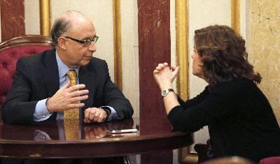 La vicepresidenta Soraya Sáenz de Santamaría charla con el ministro de Hacienda, Cristóbal Montoro, en un receso del pleno celebrado en el Congreso de los Diputados.