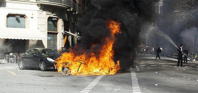 Un coche y diversos contenedores arden esta tarde durante los incidentes registrados en la confluencia de las calles Diputación y Balmes de Barcelona. EFE
