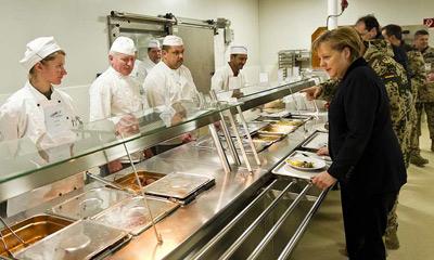 Merkel pasa con una bandeja para comer en la base militar de Mazar, en Afganistán.