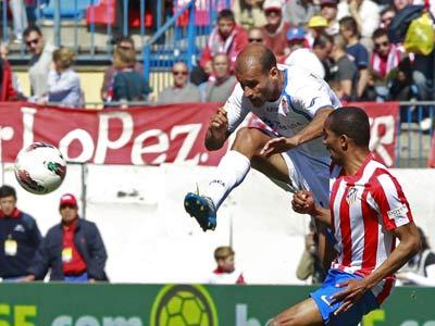 El centrocampista del Atlético de Madrid Paulo Assunsao intenta obstaculizar el lanzamiento del jugador del Granada Mikel Rico durante un partido de la Liga BBVA.