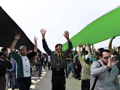 Manifestantes opositores sirios bajo la bardera rebelde.