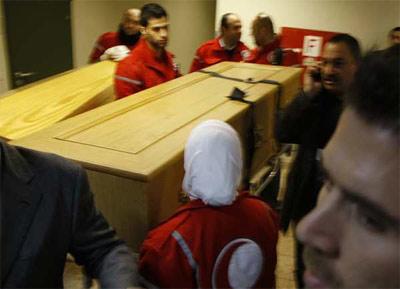 Miembros de la Media Luna Roja siria transportan los féretros con los cuerpos de los periodistas Marie Colvin y Rémi Ochlik. -