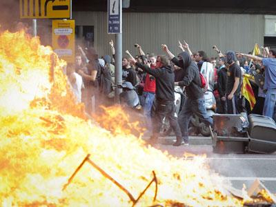 Unos manifestantes cerca de unos contenedores quemados durante la huelga general en Barcelona. AFP PHOTO/ JOSE LAGO