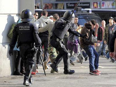 Los Mossos d'Esquadra pegando a algunos manifestantes durante la huelga general. EFE